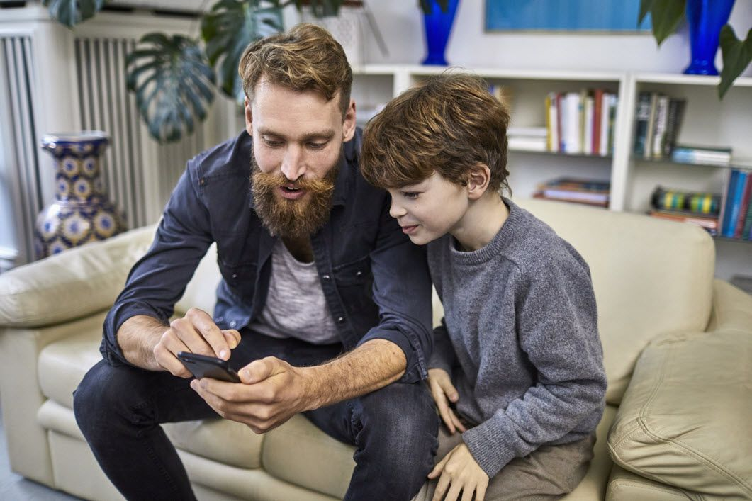 father and son looking at cell phone
