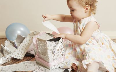 two year old girl opening a present