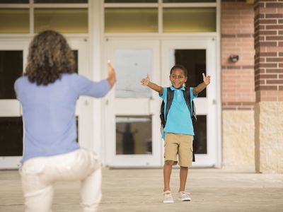 Mom and son reach out to each other on school steps.