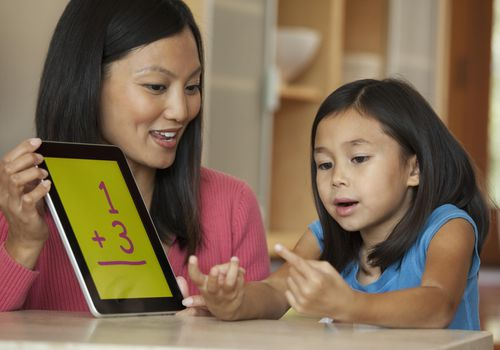 Mother using digital tablet to help daughter with arithmetic