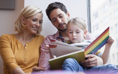 Parents reading a picture book with their daughter.