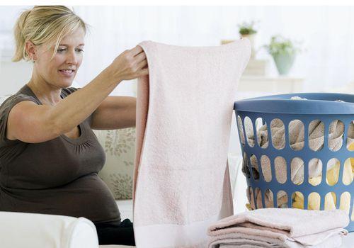 Pregnant woman folding laundry