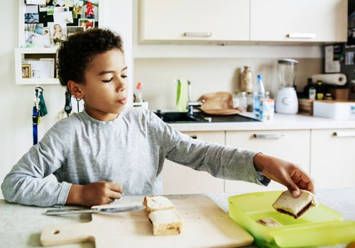 A young boy preparing a packed lunch in the kitchen at home before heading off to school.
