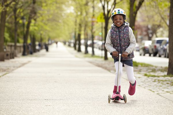 young african american girl riding a scooter