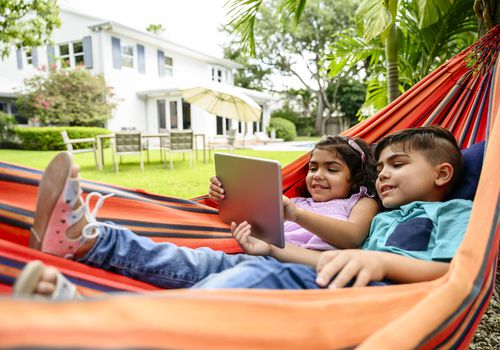 Young Latin American brother and sister relaxing outdoors in a backyard hammock and using a digital tablet.
