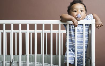 Baby boy standing in cot - stock photo