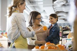 A shopkeeper and mother discussing oranges with a child