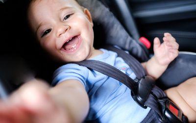 Baby boy smiling in car seat.