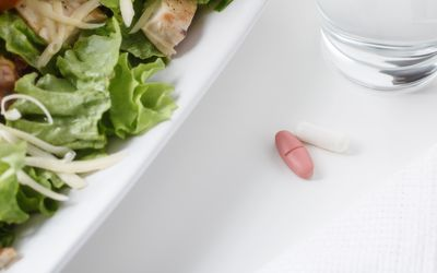 Pills next to plate of salad and cup of water