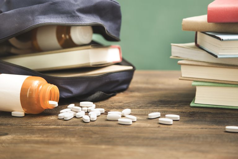 School books and backpack on desk with open pill bottle and scattered pills