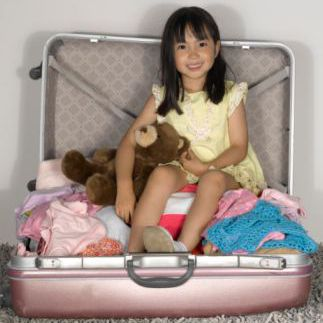 A picture of girl sitting in a suitcase