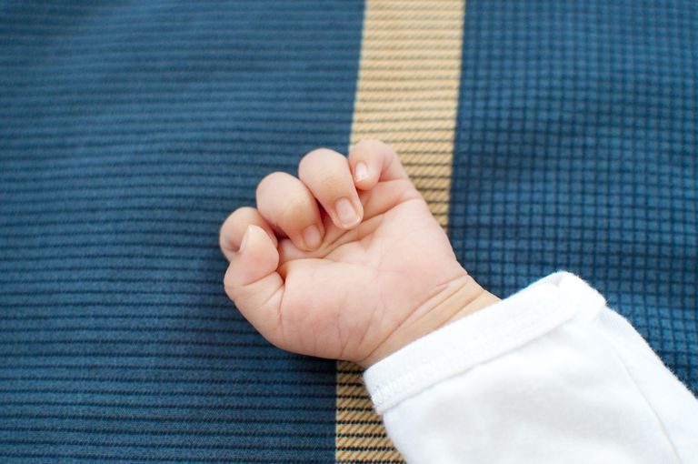 A newborn hand on blue background