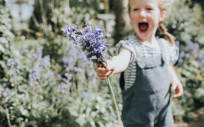 little girl in a field holding bluebell flowers