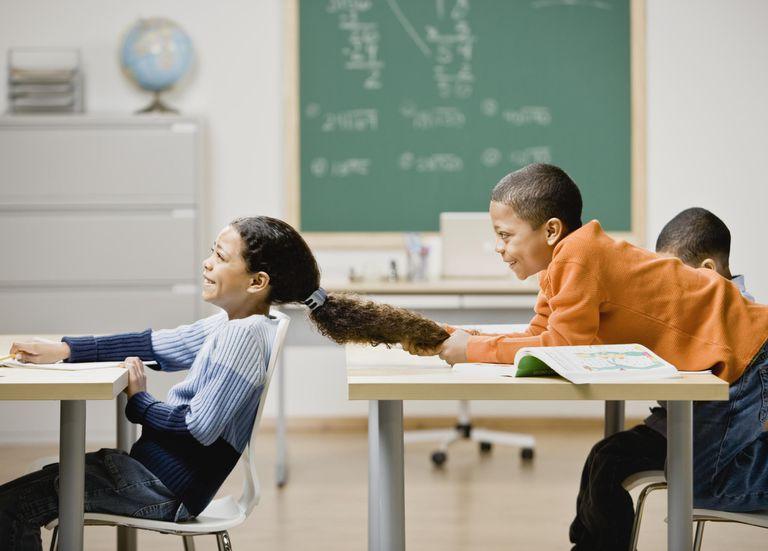 boy pulling girl's hair in school classroom