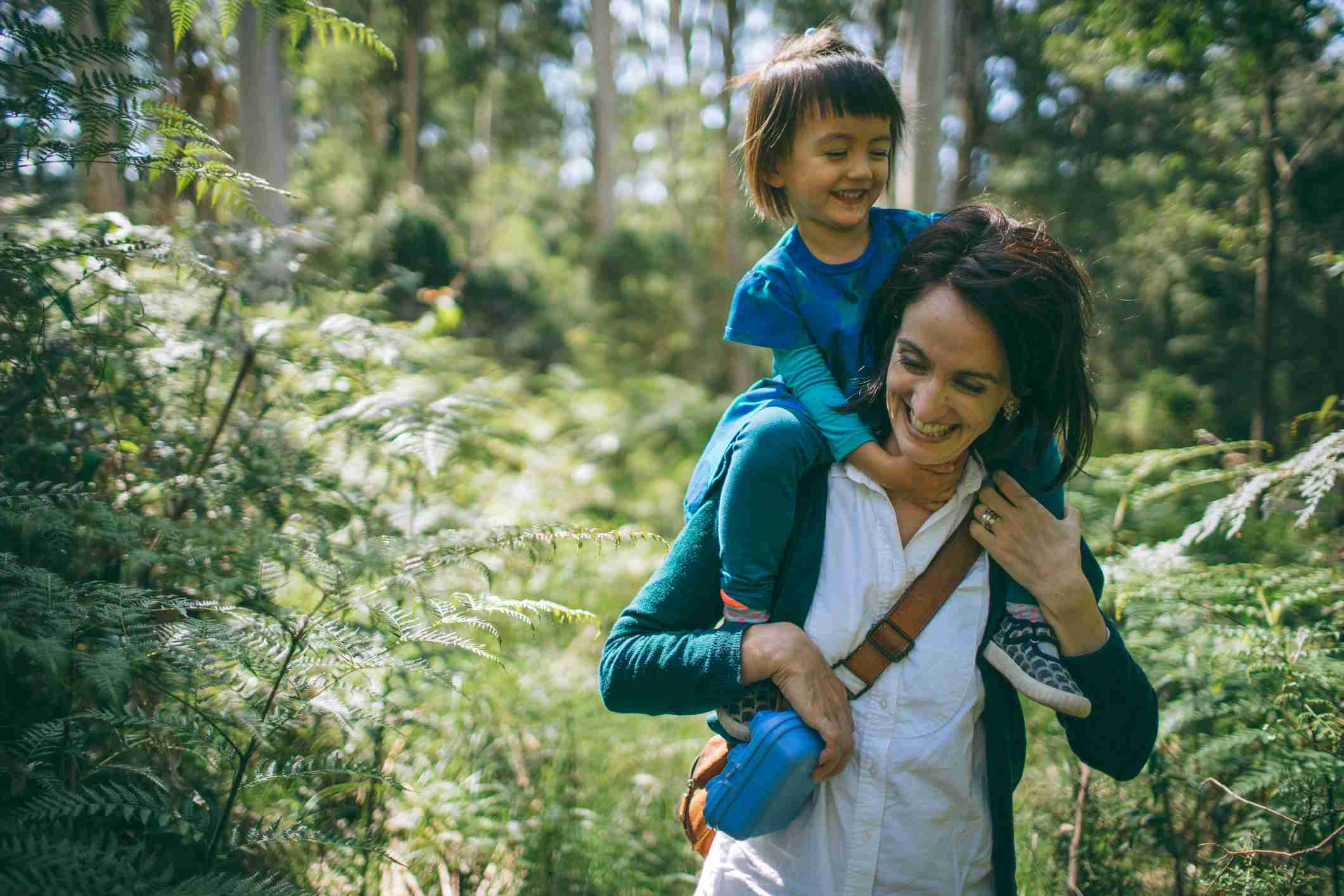 Mother hiking with her child in forest