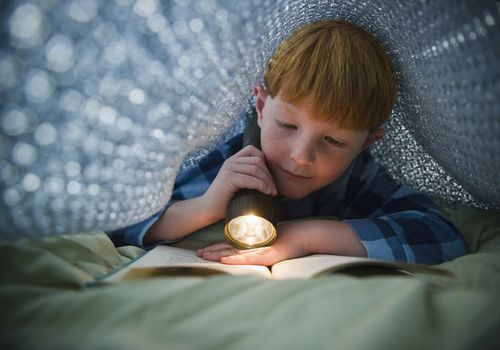 Young boy reading a book with a flashlight under the covers