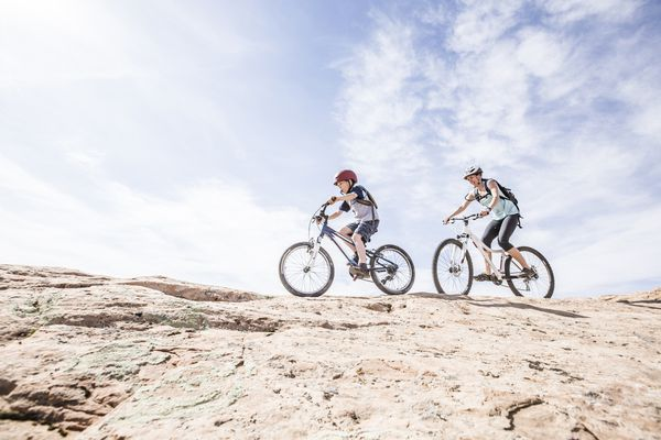 Caucasian mother and son riding mountain bikes