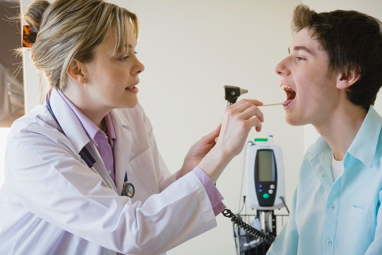 Female doctor checking teen patient's throat