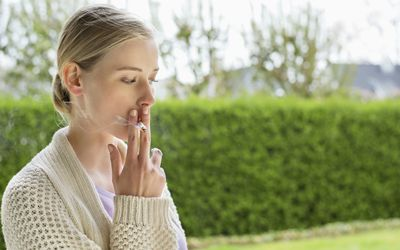 Woman smoking cigarette in park