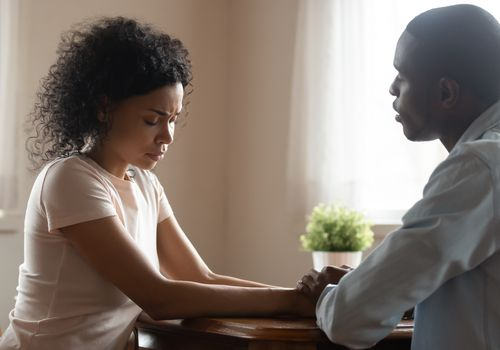 man comforting upset woman