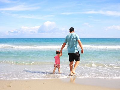 A father and daughter walking on the beach