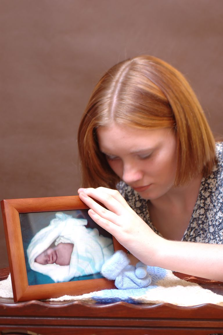 woman holding a picture of a baby she lost in stillbirth