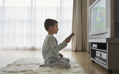 child holding remote sitting on rug in front of television