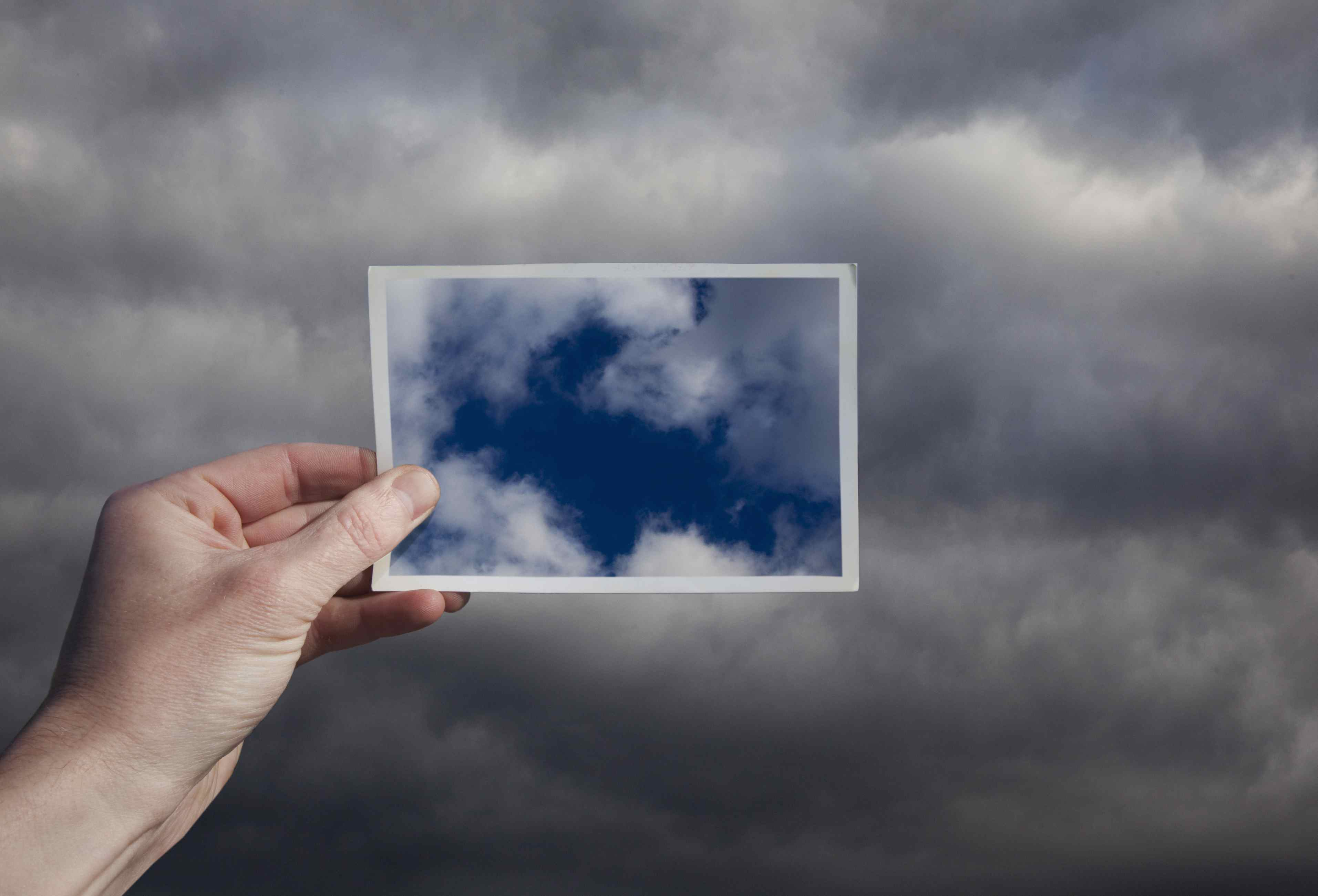woman's hand holding a picture of blue sky