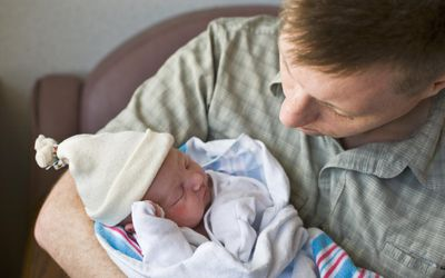 Father holding newborn baby girl