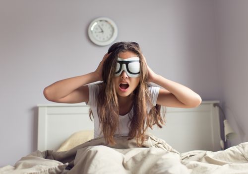 Young woman trying to get out of bed