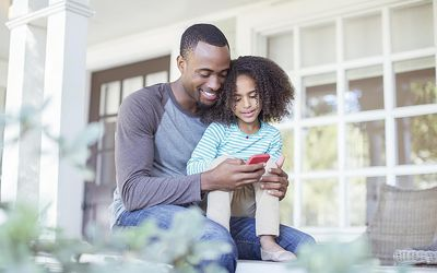 Father and daughter using cell phone on porch