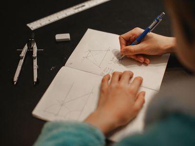 teen doing math problems in a notebook