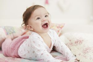 Baby girl in pink pants smiling on bed