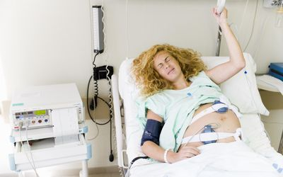 Pregnant woman in hospital bed making pained face