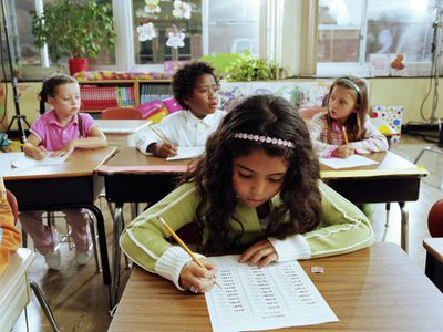 Schoolchildren (6-11) doing arithmetic in class