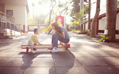 Mother and young boy talk on playground equipment