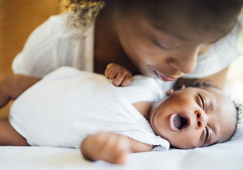Close-up of mother looking at cute newborn daughter yawning while lying on bed