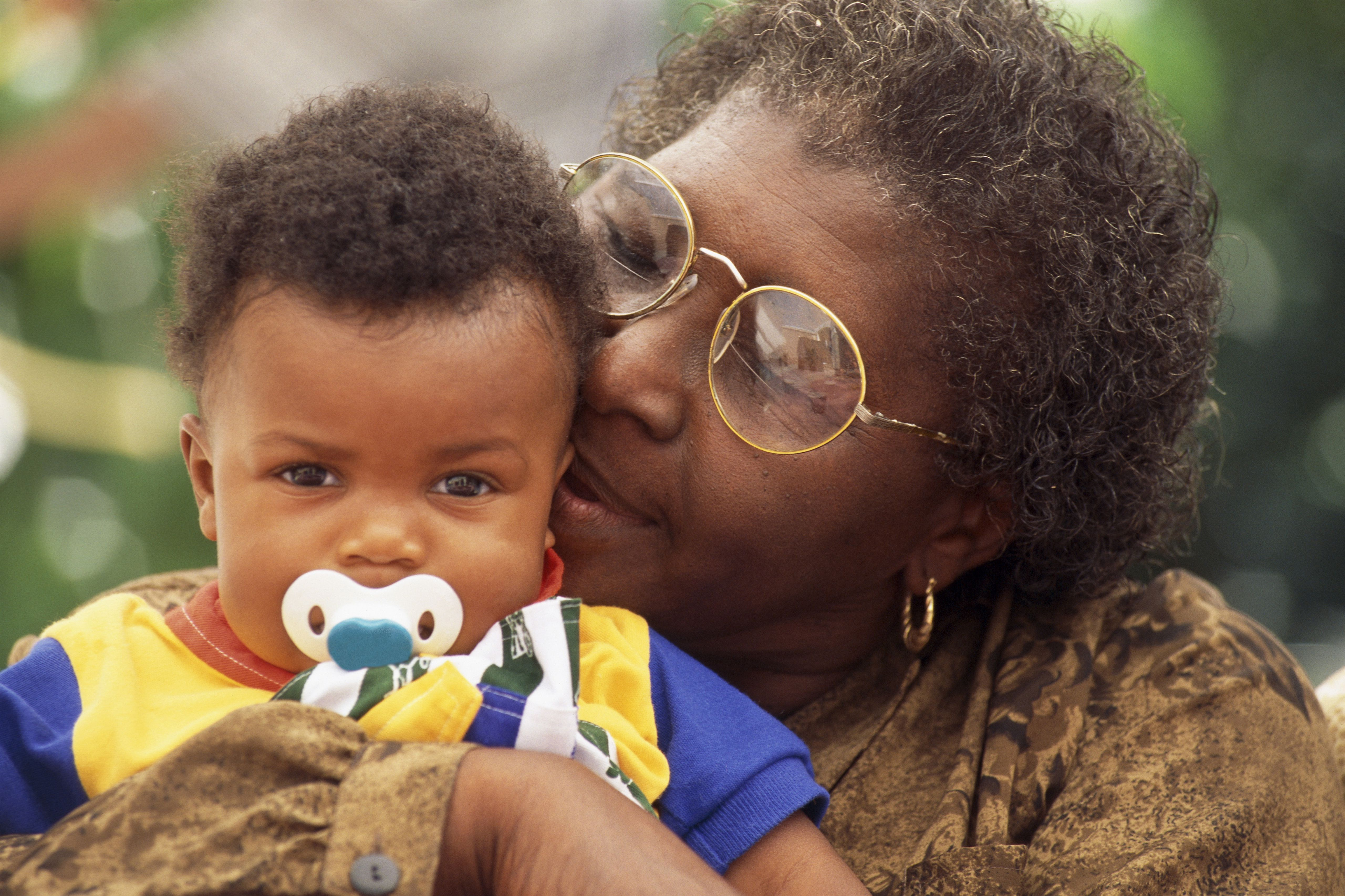 Senior African-American woman kissing her grandson on the ear.