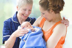 Proud grandmother watches daughter holding newborn grandson