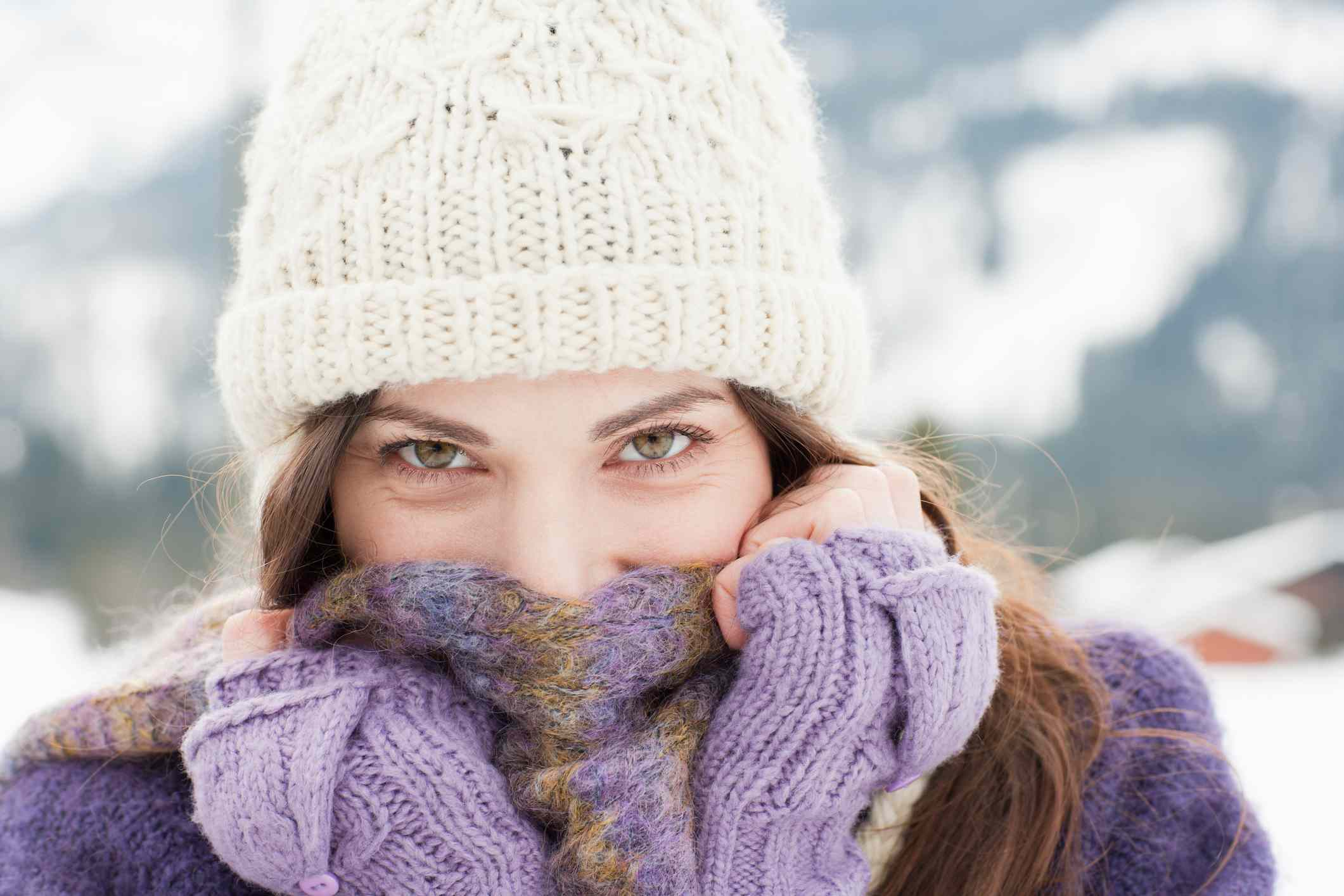 young woman wearing knit beanie and covering her face with scarf
