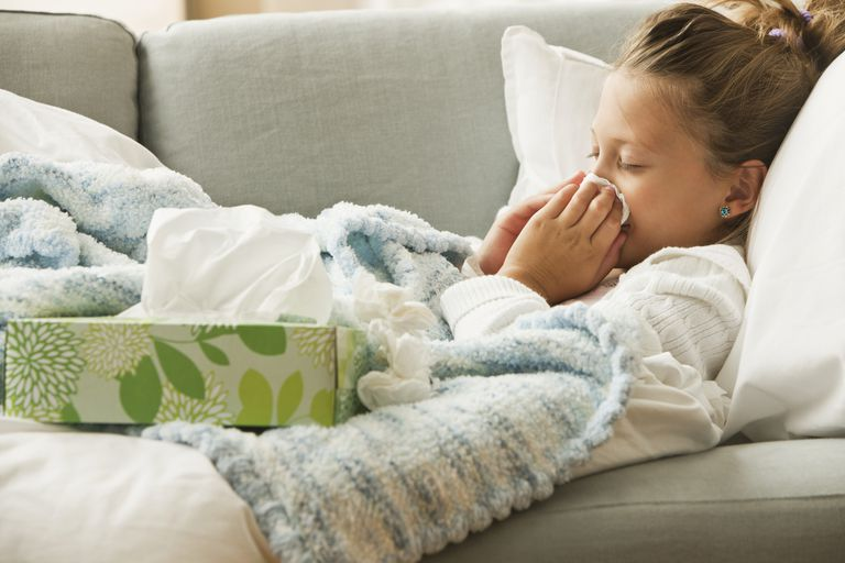 young girl blowing nose sick on couch
