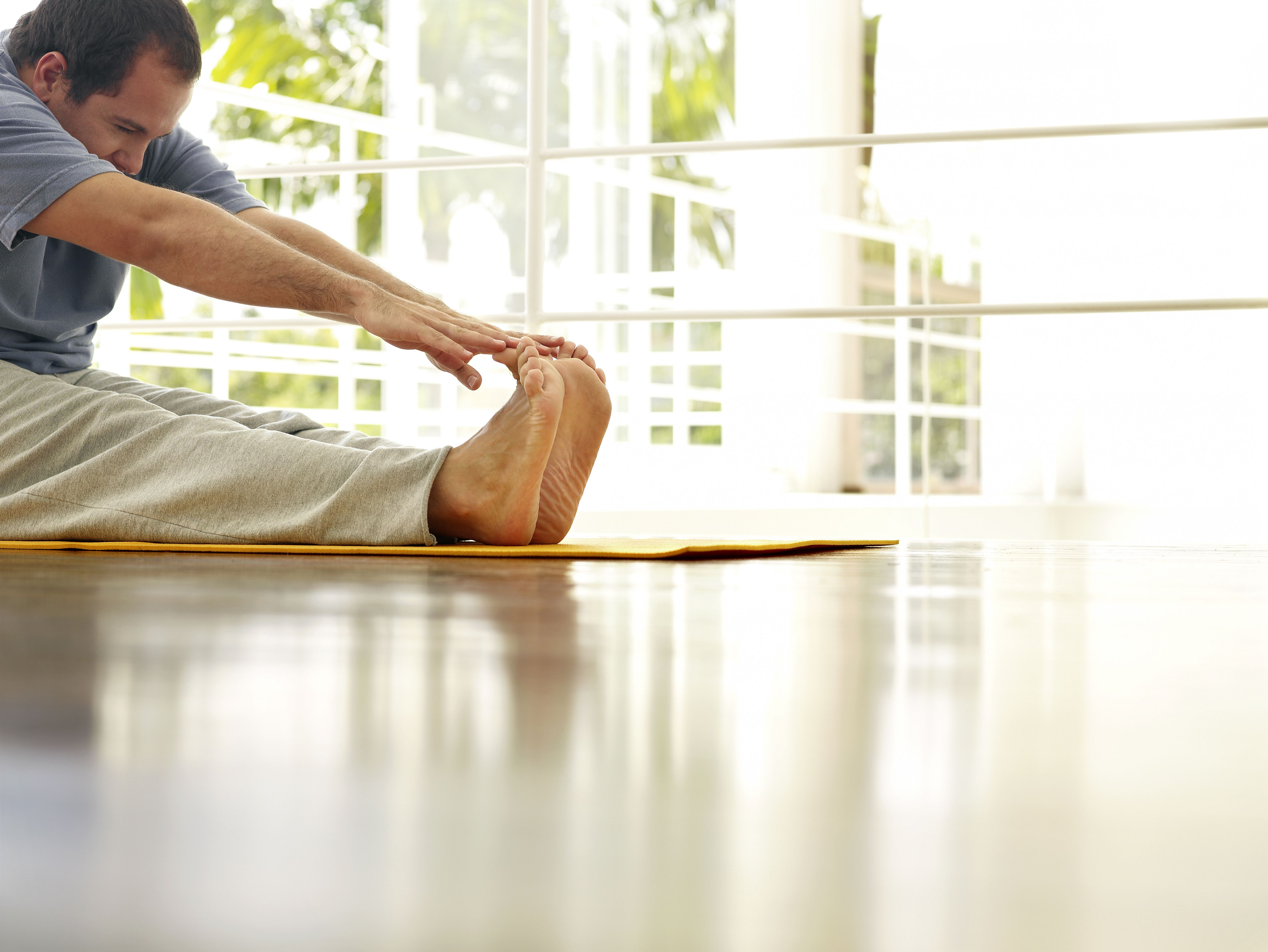 Man stretching in the house, working out to lose weight