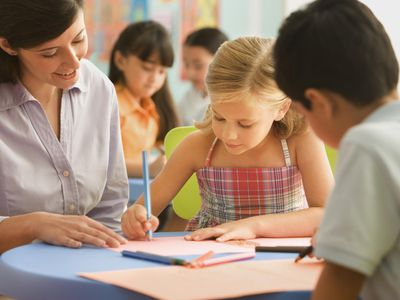 Children drawing pictures with teacher