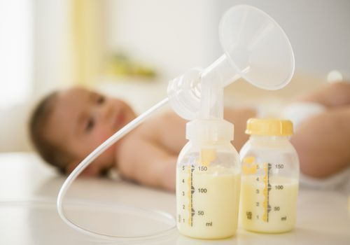 breast pump and bottles in front of baby