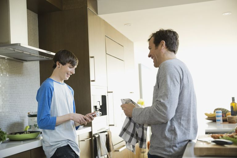 Father and son talking in kitchen