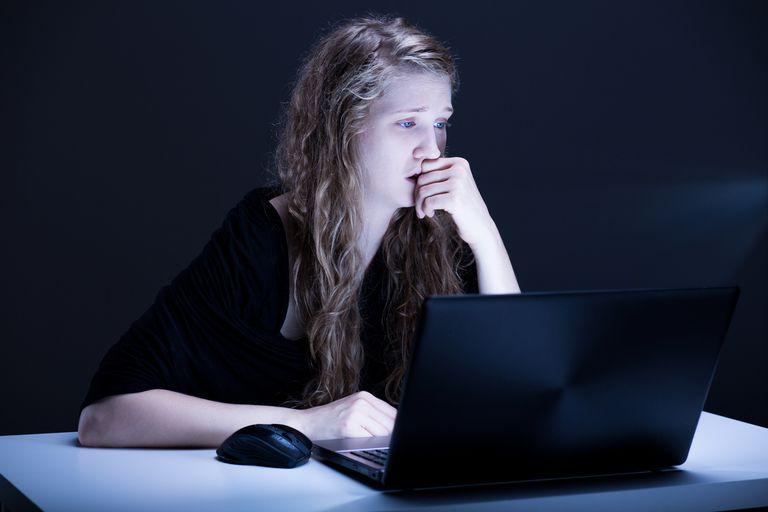 upset teen girl looking at computer