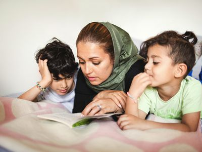 mom-reading-to-her-kids-on-bed