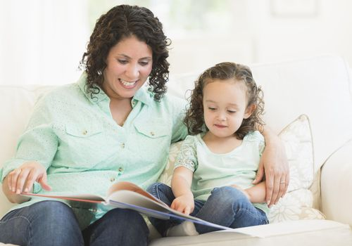 Mixed race mother reading with daughter