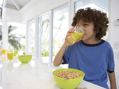 Boy at table, drinking orange juice