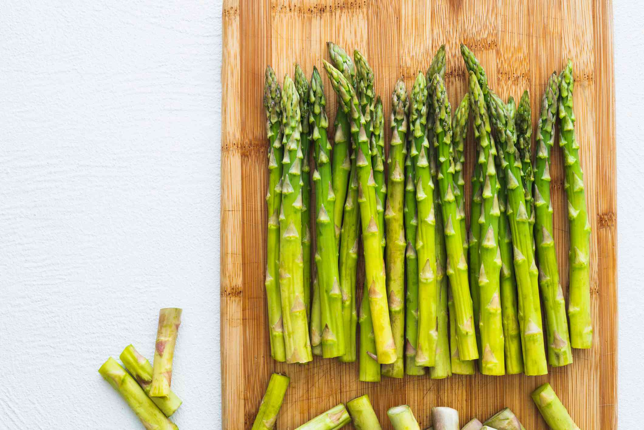 Asparagus on a Wooden Chopping Board, Top View, Close Up on White Background. Cooking, Vegetarian, Healthy Eating
